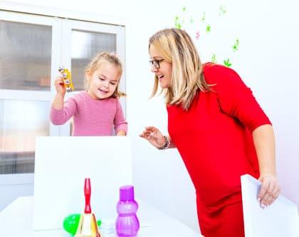 teacher helping the little girl