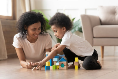 happy adult woman assisting learning activity with the toddler using building bricks