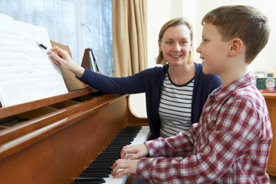 young boy with music teacher having a lesson on piano